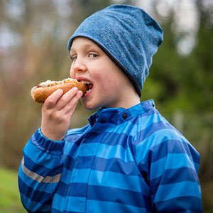 Cropped image of a boy eating a hot dog