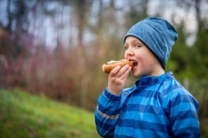 Original image of a boy eating a hot dog with grass and plants in the background